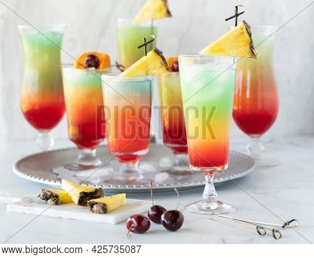 A Tray Of Colourful Mocktails With One Out In Front, Ready For Drinking.