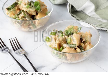 Close Up View Of Two Bowls Of Creamy Potato And Bean Salad Ready For Eating.