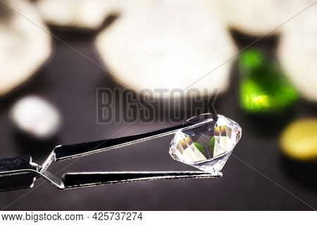 Cut Diamond Held By A Jeweler's Tweezers, With Rough Diamond Stones In The Background, Spot Focus