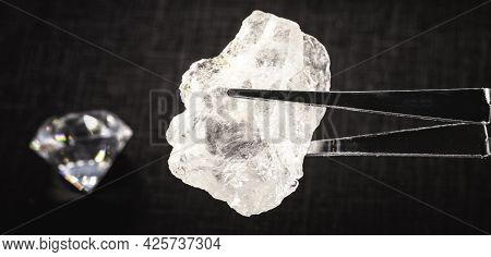 Rough Diamond Or Crystal Held By A Jeweler's Tweezers, With Jewels In The Background, Spot Focus