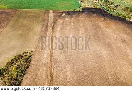 Tractor Plowing Field In Spring. Beginning Of Agricultural Season. Cultivator Pulled By A Tractor In