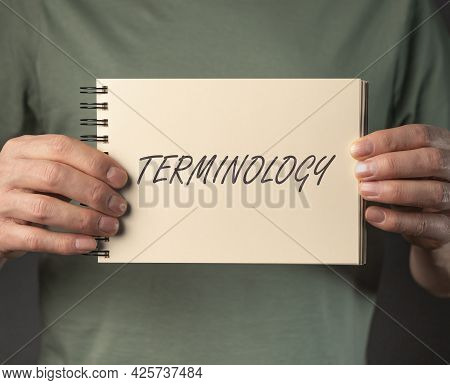 Terminology Word On Notebook In Male Hands.