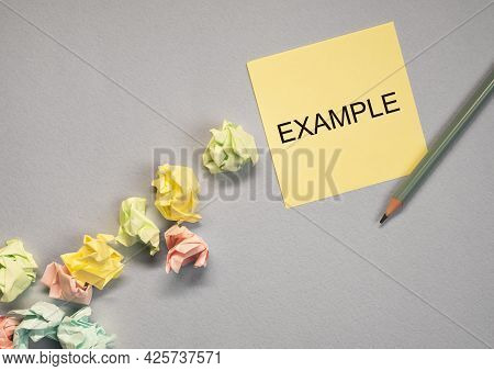 Example Word On Yellow Sticky Note On Grey Background With Crumpled Papers.