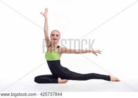 She Has What It Takes. Gorgeous Blonde Female Gymnast Sitting Gracefully On The Floor Against White