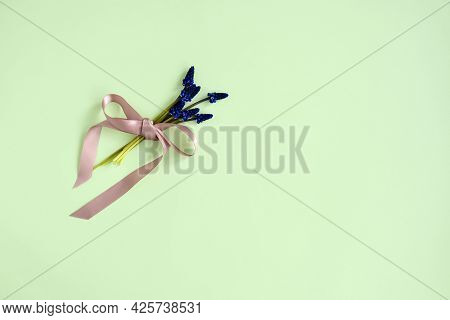 Bouquet Of Tender Hyacinths Tied With Pink Satin Ribbon, On Green Background. Top View. Copy Space.