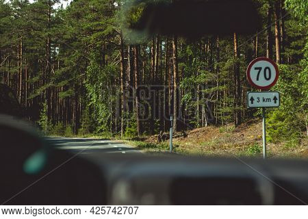 View From The Driver\'s Seat On An Asphalt Road Leading Into The Woods With A Speed Limit Sign.