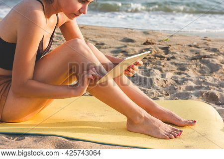 Young Woman Sitting On A Yellow Yoga Mat, Using Tablet On The Beach. Wireless Communication Concept