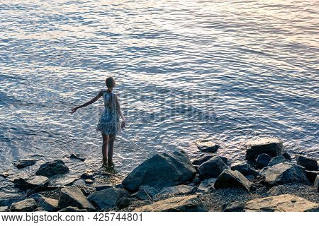 Teenage Girl In A Summer Dress Stands In The Water Near The Shore And Enjoys The Morning Sun