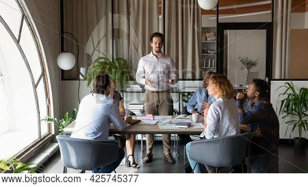 Confident Businessman Mentor Leading Briefing With Diverse Employees In Office