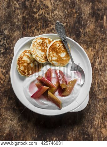 Delicious Breakfast - Greek Yogurt With Rhubarb Sauce And Mini Pancakes On A Wooden Background, Top