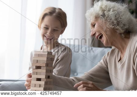 Laughing Senior Grandmother Enjoy Playing Board Game With Little Granddaughter