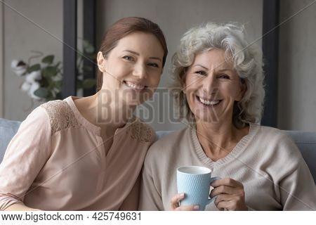 Elderly Mother Grown Daughter Sit On Couch Drink Coffee Talk