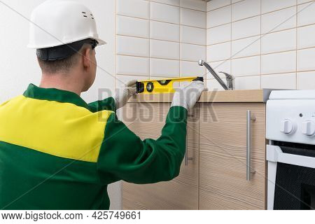 A Specialist Will Check The Evenness Of The Installation Of Kitchen Furniture With A Tool