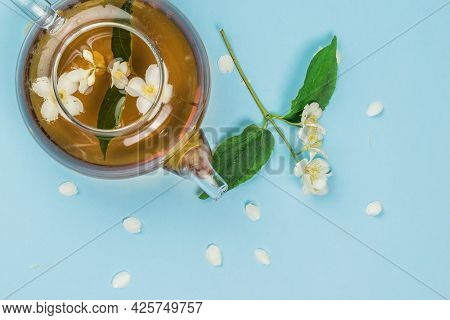 Jasmine Flowers Brewed In A Teapot On A Blue Background. An Invigorating Drink That Is Good For Your