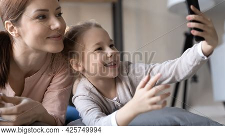 Little Daughter Relax With Mommy Hold Smartphone Take Selfie