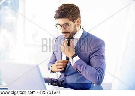 Shot Of Young Businessman Wearing Suit While Sitting At Office And Tie Knot.