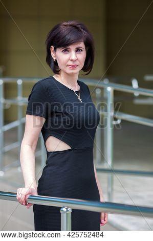 Strict Brunette In A Black Dress Near An Office Building On The Street.