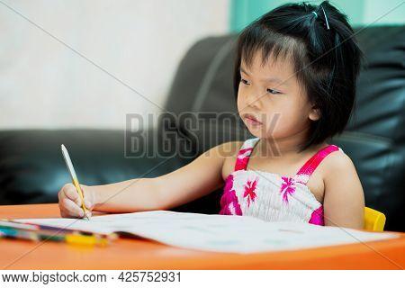 Asian Child Is Sluggish Having Sleepiness While Doing Homework. Girl Close Half Eyes. Cute Kid Aged