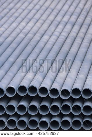 Stack Of Gray Galvanized Pipes Material Inside Of Construction Site In Vertical Frame