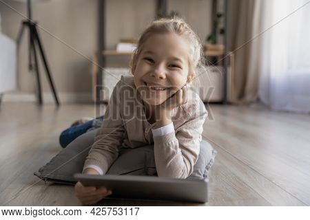 Smiling Preteen Girl Lying On Warm Floor Holding Digital Tablet