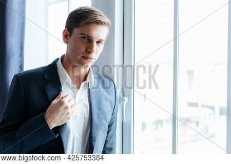 Confident Business Man Stand Near Window At Office Wearing Suit And Shirt Portrait Handsome Young Ca