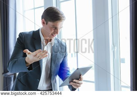Happy Young Business Man Using Digital Tablet For Chatting With Customer Or Team In Office At Compan