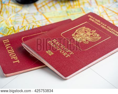 Close-up Of Two Russian Passports Lying On The Map Of The City. The Concept Of Travel And Migration