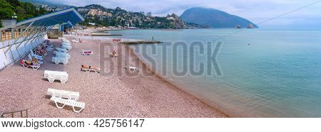 Beach On The Black Sea Coast With Tourists Who Relax And Sunbathe On A Summer Sunny Day (panoramic S