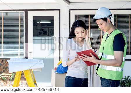 Asian Attractive Woman And Male Engineer, Looking At A Report To Discuss About Renovating The Old Ho