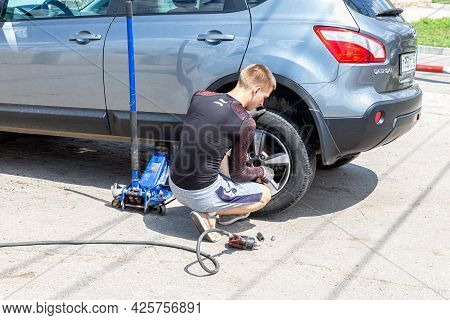 Samara, Russia - July 4, 2021: Mechanic Is Repairing Vehicle. Repairman Is Removing Wheel By Electri