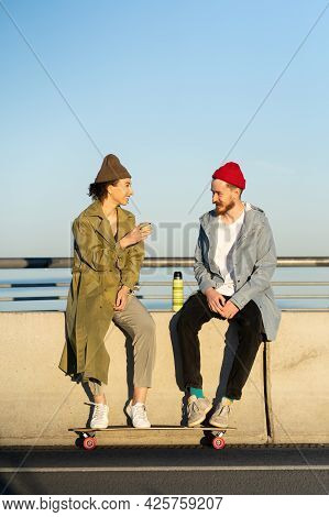 Young Couple Of Skateboarders Relaxing After Active Skateboarding Training Sitting On Concrete Bridg
