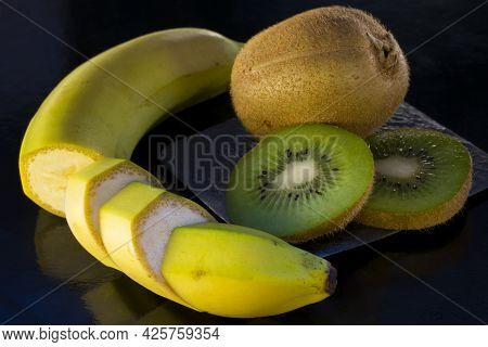 Banana And Kiwi Isolated On Black. Delicious Banana And Juicy Kiwi, Cut Into Slices. Many Vitamins I