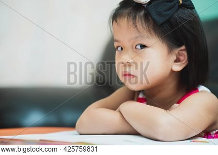 Asian Girl Show Displeasure And Strongly Resist Doing Homework. Child Sat With Arms Crossed And Glan