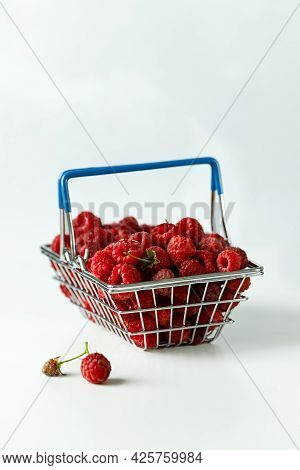 Mini Grocery Shopping Basket With Fresh Raspberries On A Grey Background. Food Photo