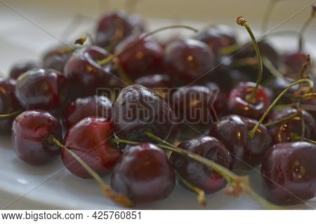 Red And Ripe Cherries On A White Plate