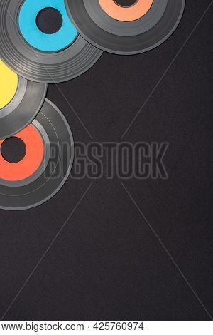 Multi Colored 7 Inch Single Vinyl Records On A Black Background With Empty Space For Text. Top Down