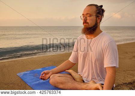 Man Practices Yoga Meditation Sitting In Padmasana During Sunrise. Man Sits In Lotus Position At Bea