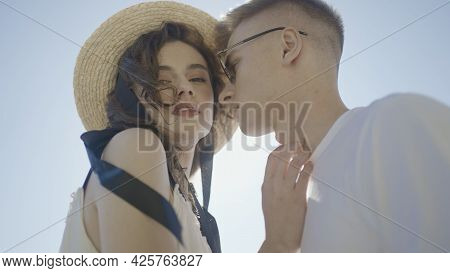Beautiful Young Couple On Background Of Glowing Sun. Action. Stylish Couple Look At Each Other With