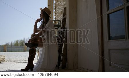 Profile Of Beautiful Young Woman In Dress. Action. Side View Of Attractive Woman In Dress Sitting In