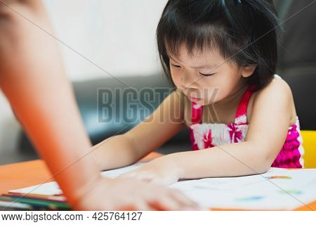 Little Child Doing Homework On An Orange Table. Blurred Hand Of The Parents Arm At The Desk, Strict
