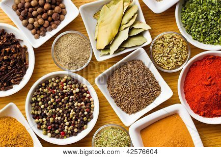 Various spices and herbs on wooden table.