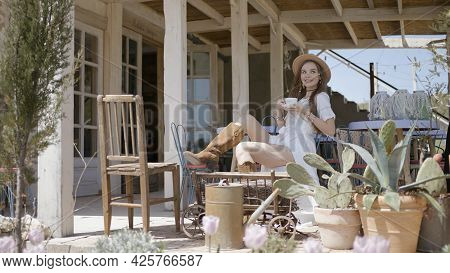 Beautiful Young Woman Drinking Tea On Veranda. Action. Attractive Woman In Beautiful Dress Is Drinki