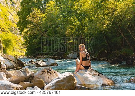 Smiling And Happy Young Woman Looking At Camera Sitting Near A River In The Forest. Rio Cares In Pic