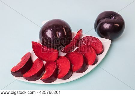 On A White Saucer There Is A Large Plum Cut Into Wedges, Next To It There Are Two More Plums.