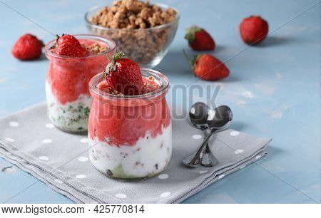 Granola Crispy With Strawberry, Spinach And Natural Yogurt In Glass Jars On Light Blue Background. D