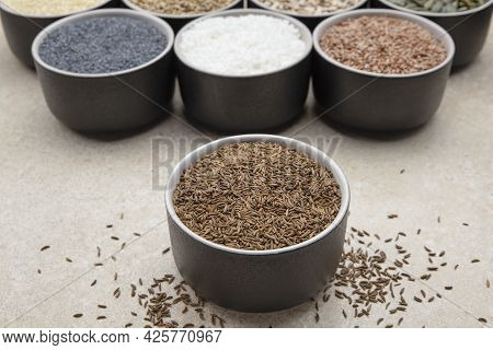 Caraway Seeds. Cup With Caraway Seeds On A Background Of Various Seeds In Black Containers On A Marb