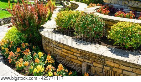 Landscape Design Of Nice Home Garden, Landscaping With Retaining Walls And Flowerbeds In Residential
