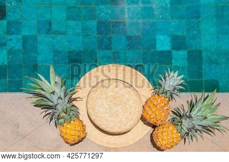 Straw Hat And Three Pineapples By The Refreshing Pool, Viewed From Above