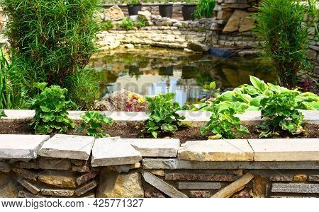 Landscape Design Of Nice Home Garden, Landscaping With Retaining Walls, Pond And Flowerbeds In Resid