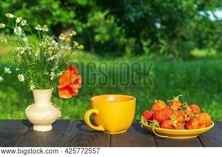 Summer Still Life Of A Plate With Strawberries And Coffee On A Table With Flowers. Summer Morning Or